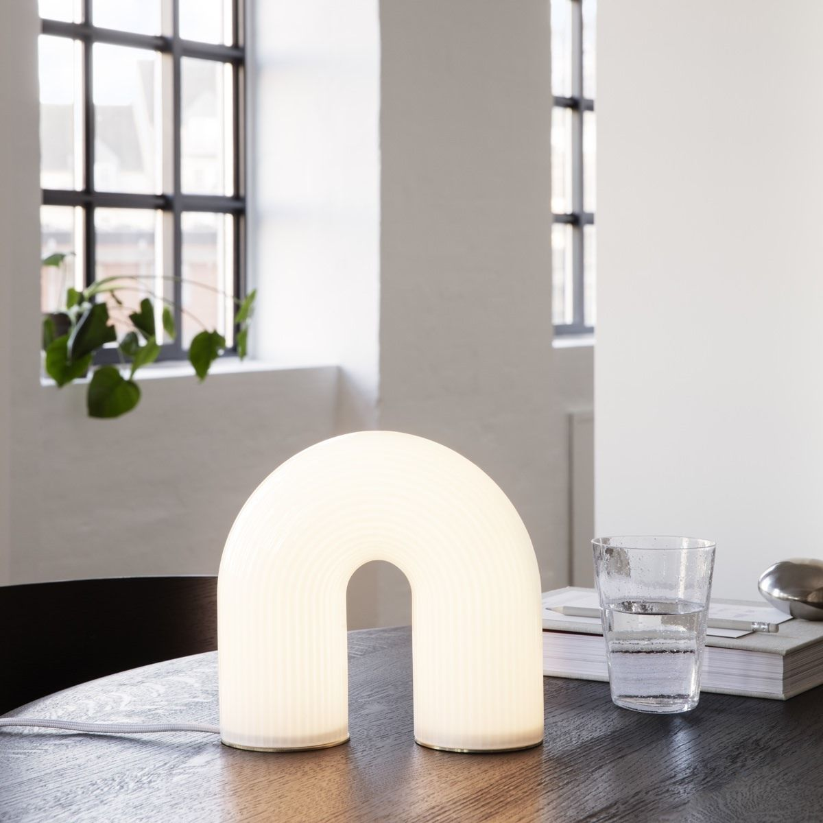 Ferm Living Vuelta Table Lamp switched on, on a desk