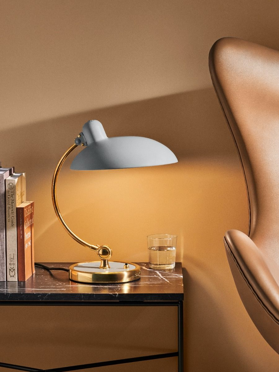 Kaiser Idell6631-T Luxus in brass, and easy grey on a side table next the the Fritz Hansen egg chair
