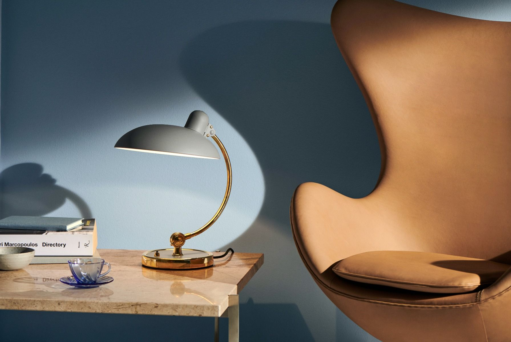 Kaiser Idell6631-T Luxus in brass, and easy grey on a side table next to an egg chair