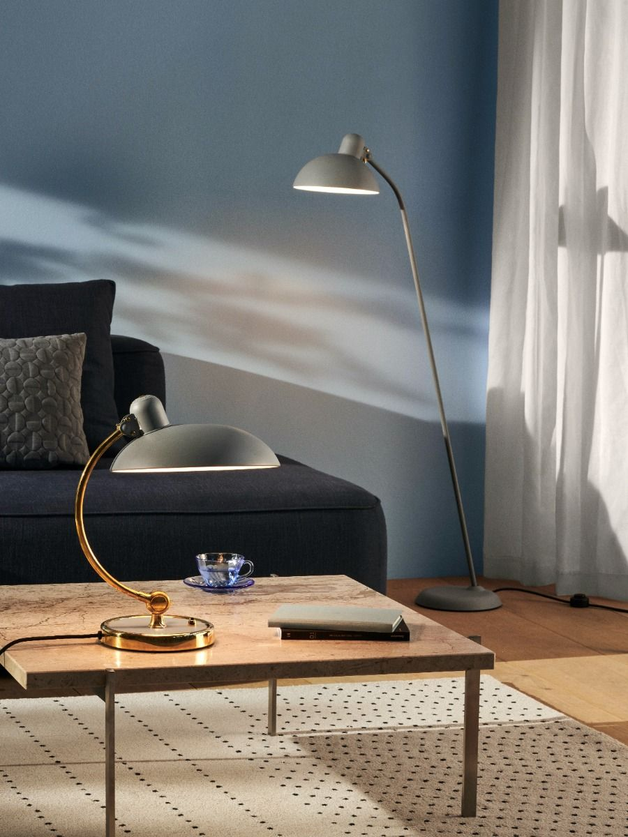 Kaiser Idell6631-T Luxus in brass, and easy grey on a sofa with the floor lamp