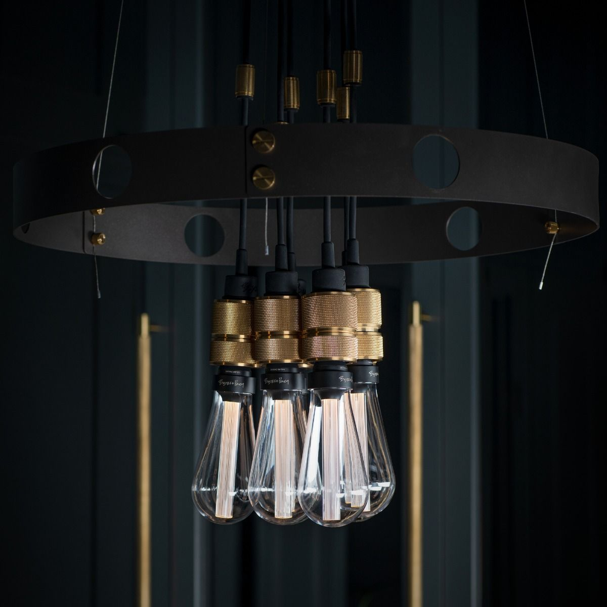 Buster + Punch Hero Pendant In Gaphite and Brass detail hanging in front of wardrobe doors