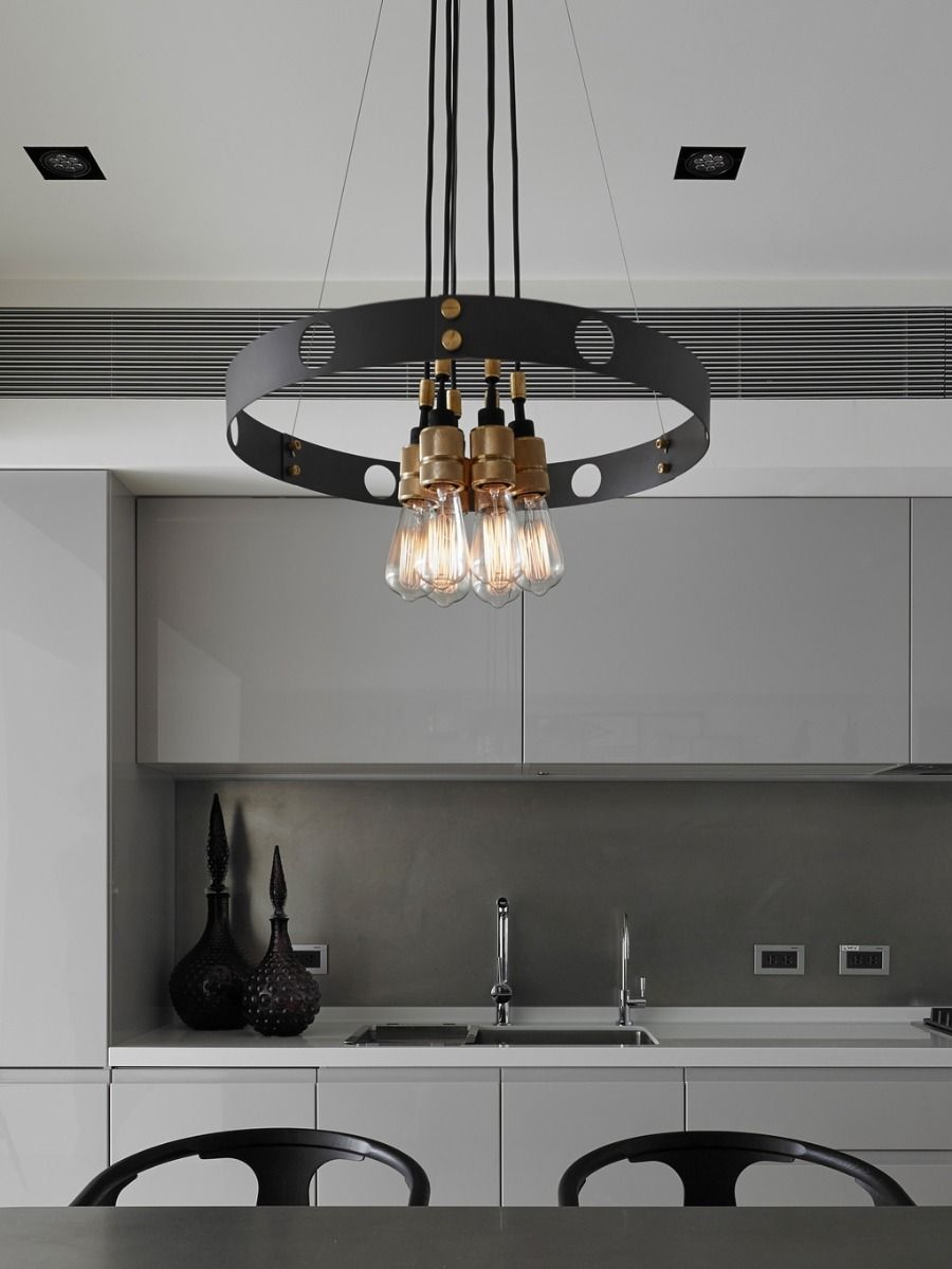 Buster + Punch Hero Pendant In Gaphite and Brass hanging above a table in a kitchen