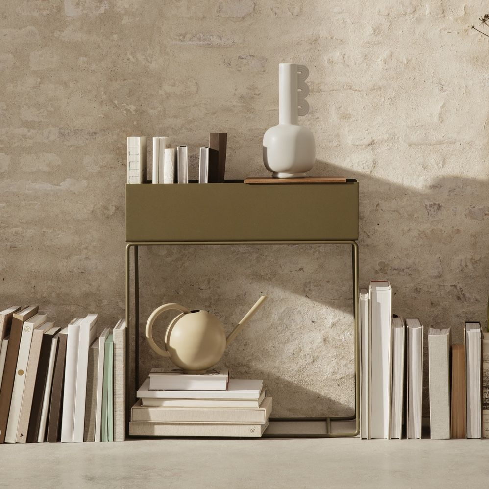 ferm living plant box in olive green with books leaning against it.