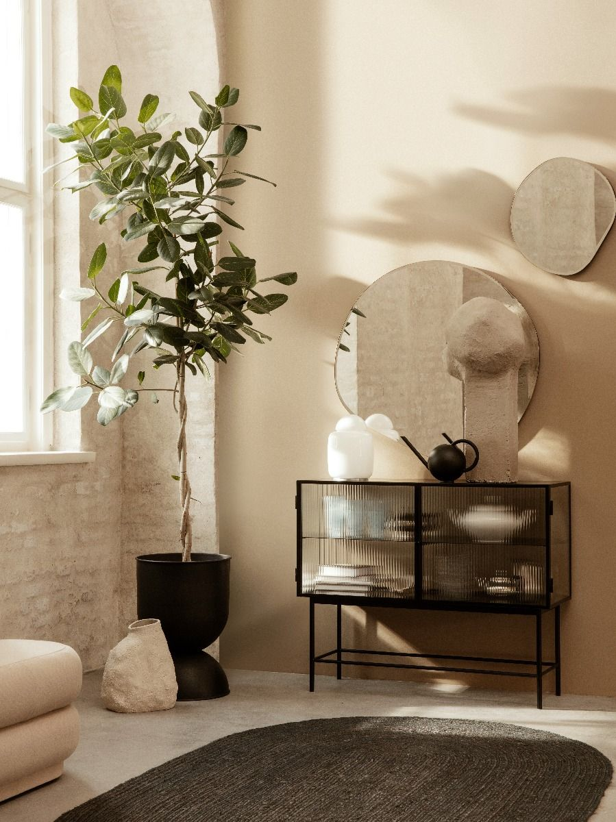 Ferm Living Pond Mirror Extra large hanging above a haze sideboard with a small pond mirror in a beige interior