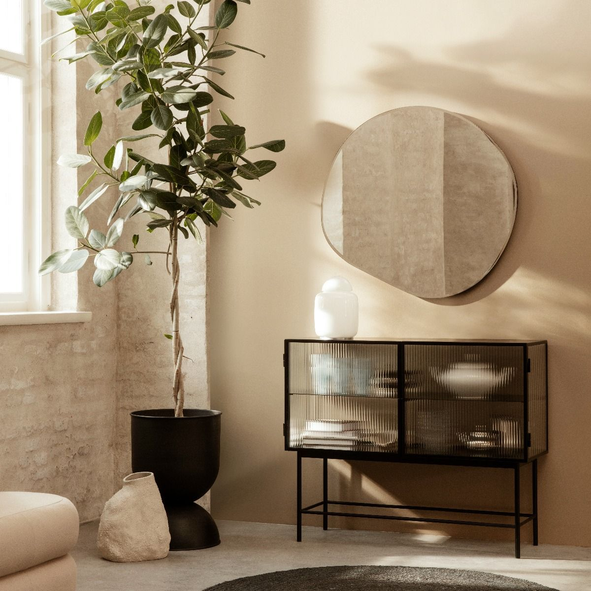Ferm Living Pond Mirror Extra large hanging above a haze sideboard