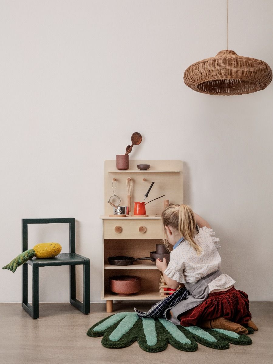 a little girl playing with the Ferm Living Toro Play Kitchen