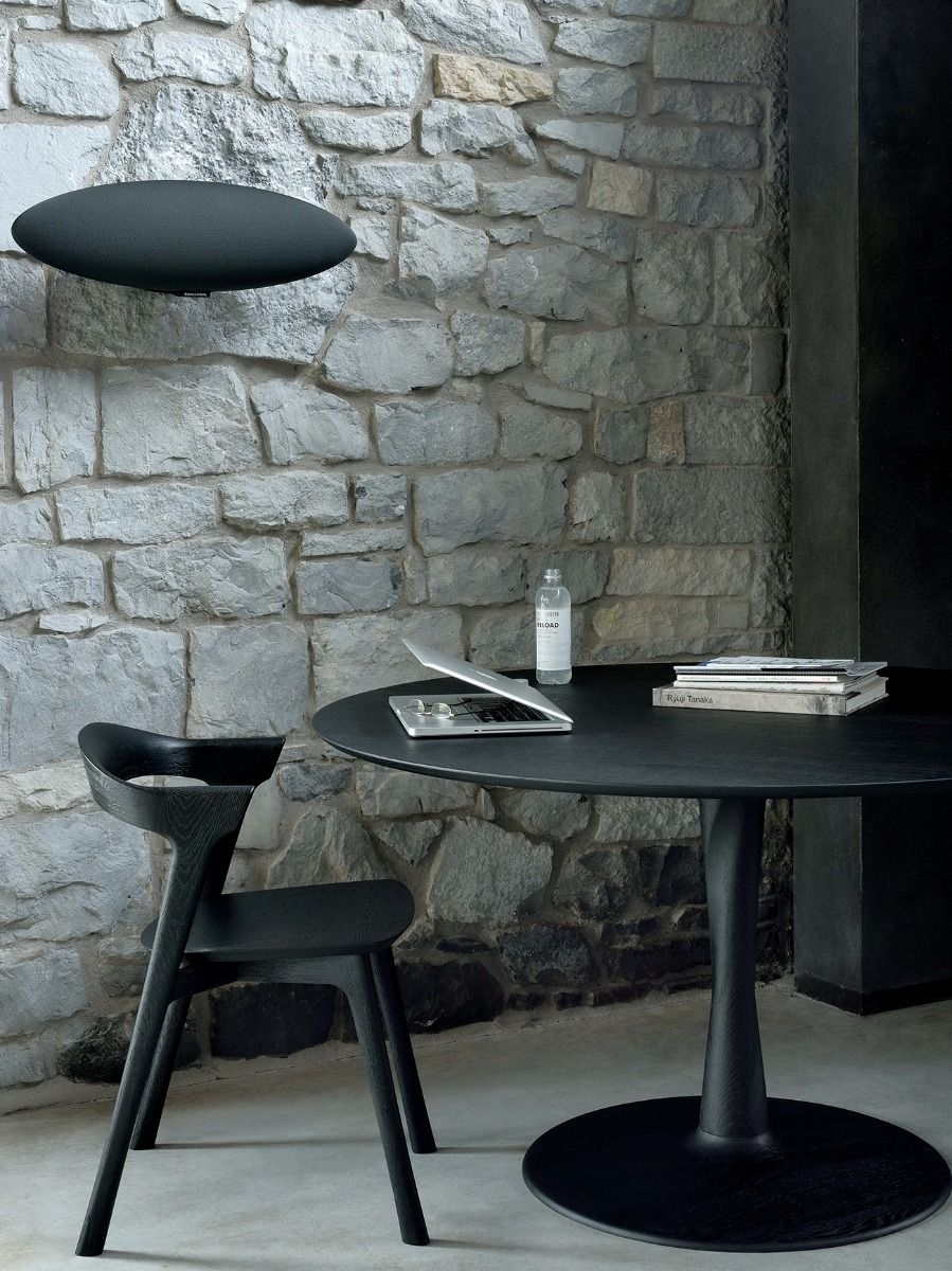 Ethnicraft Torsion Table in black with a stone wall and black bok chair and laptop