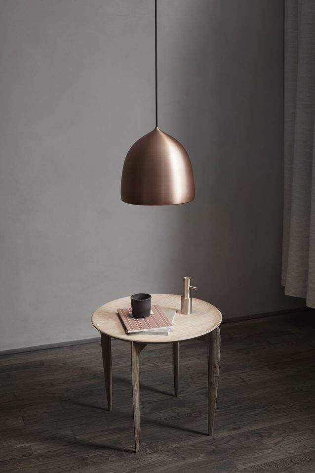 Fritz Hansen Suspence Copper Pendant Light above a coffee table