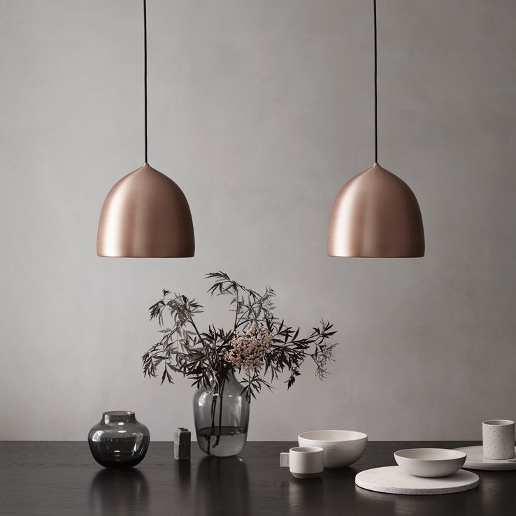 two Fritz Hansen Suspence Copper Pendant Lights above a kitchen table