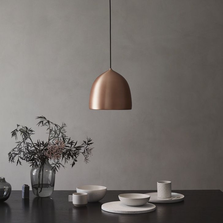 Fritz Hansen Suspence Copper Pendant Light above a table with dishes on