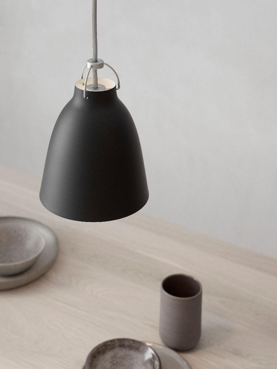 fritz hansen caravaggio pendant light matt black p1 hanging over oak table