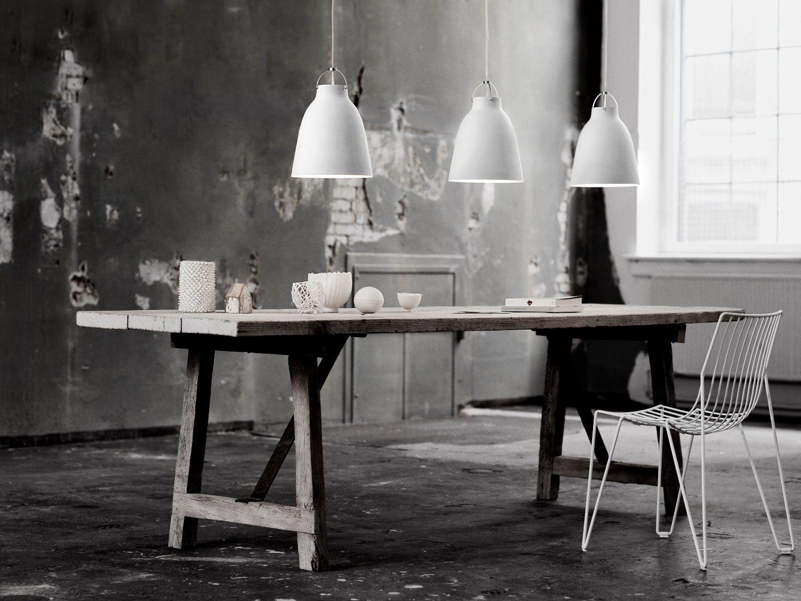 fritz hansen caravaggio pendant light matt white three hanging over a table