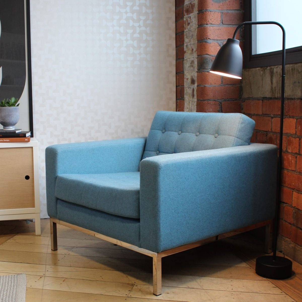 Robin Day Club armchair in blue fabric next to tv cabinet