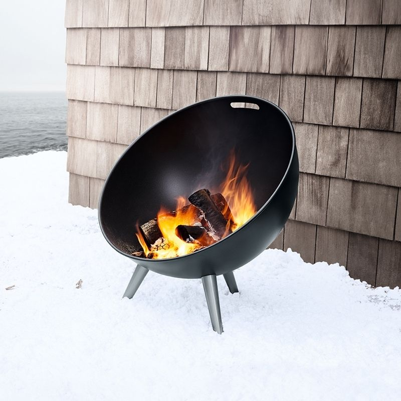 eva solo fire globe lit outside in a snowy environment with a wooden board wall behind