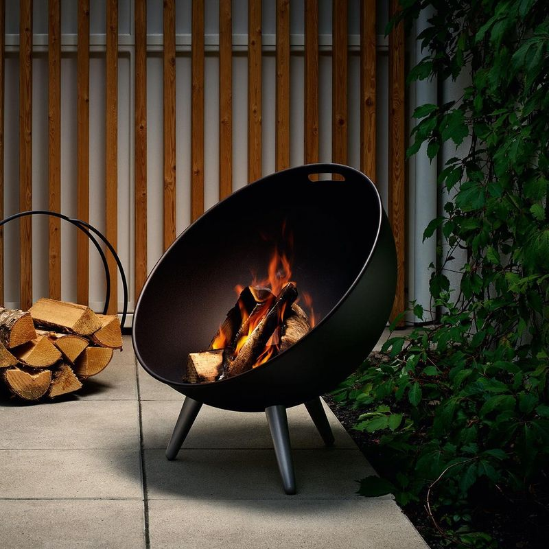 eva solo fire globe lit outside with a log holder and green climbing leaves behind