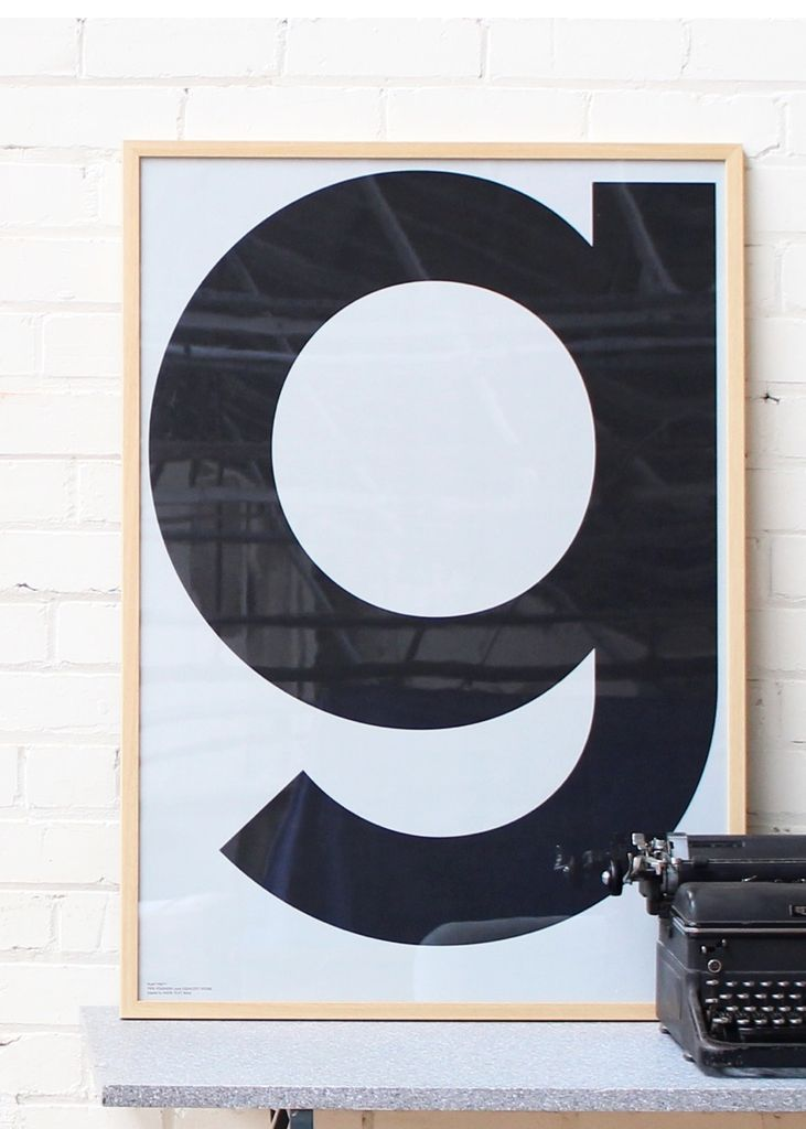 playtype grey g poster in a wooden frame in front of a white brick wall with a typewriter