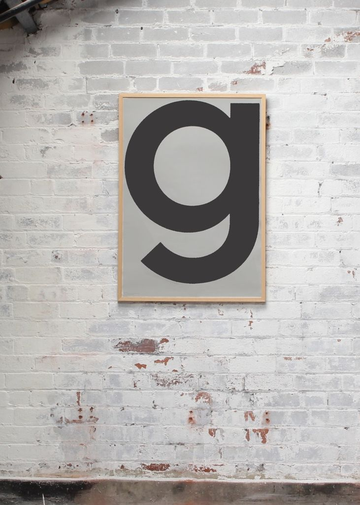playtype grey g poster on a white brick wall in a warehouse loft