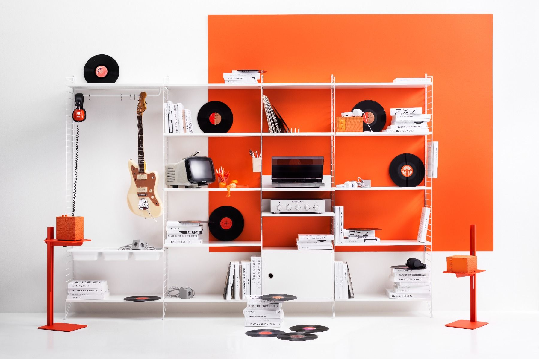 string shelving system with records on an orange wall