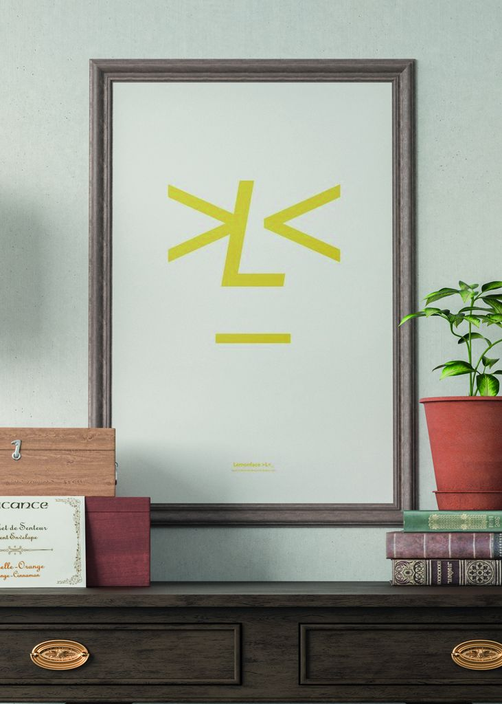 playtype lemonface poster in a brown frame with books and a potted plant beside