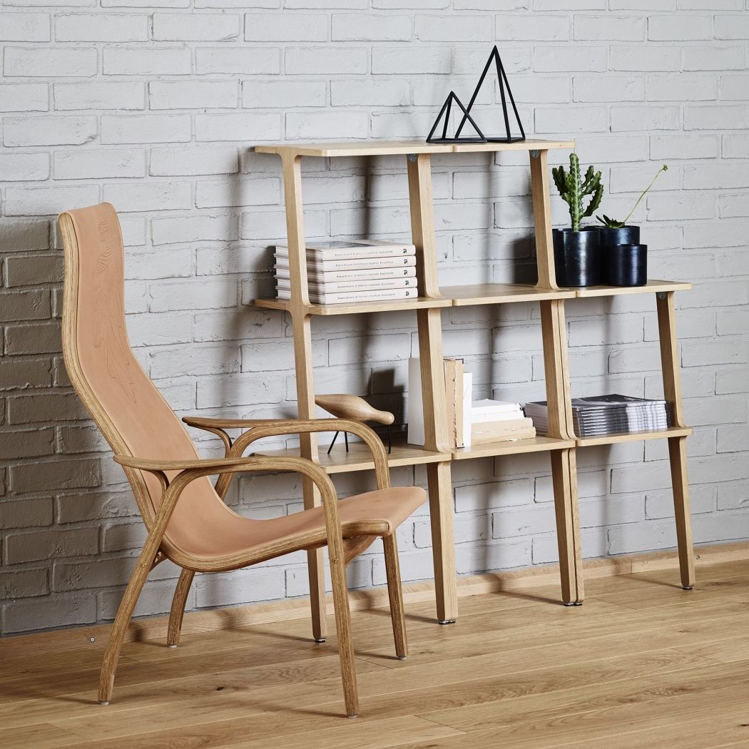 Swedese Libri shelf in oak leaning against a grey brick wall