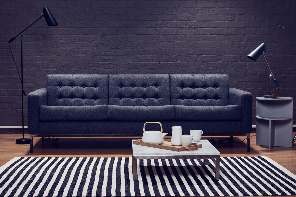 Robin Day Club Sofa in front of brick wall with birdy lamps