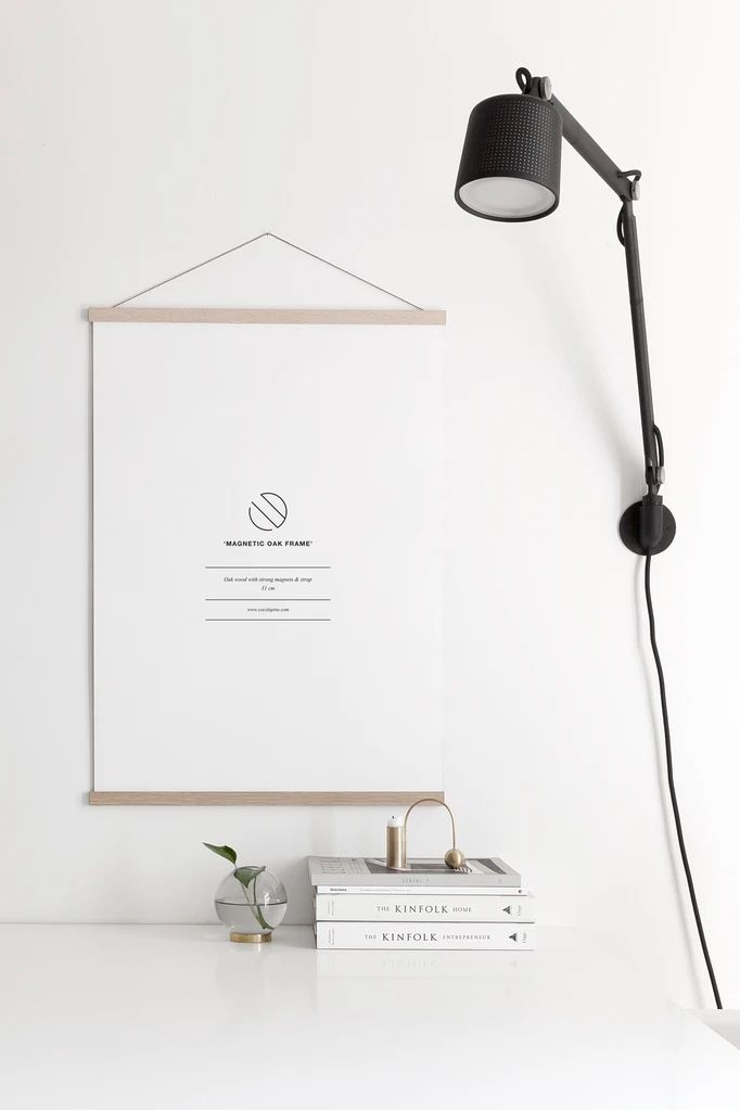 Coco Lapine oak poster hanger on a white wall next to a wall light