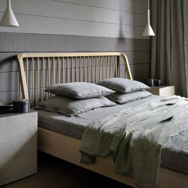 Ethnicraft Oak Spindle Bed with grey bedding and bedside pendant lights