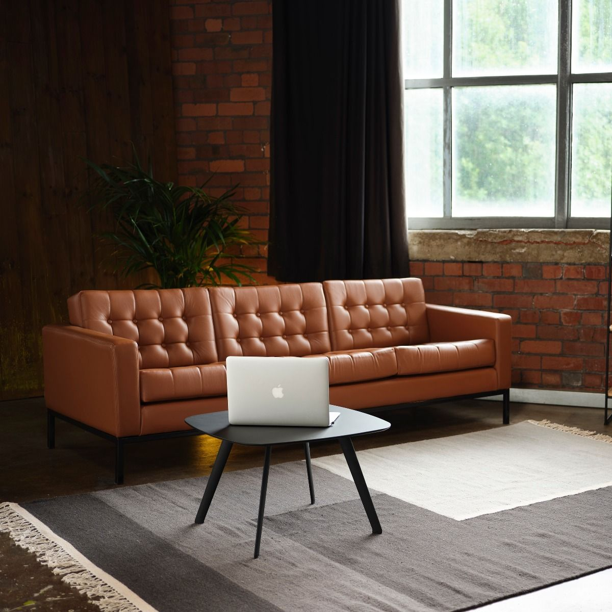 Robin Day Club sofa in Copper brown leather with coffee table and laptop