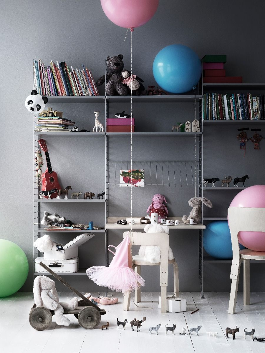 Grey String shelving system in kids room including wire magazine rack