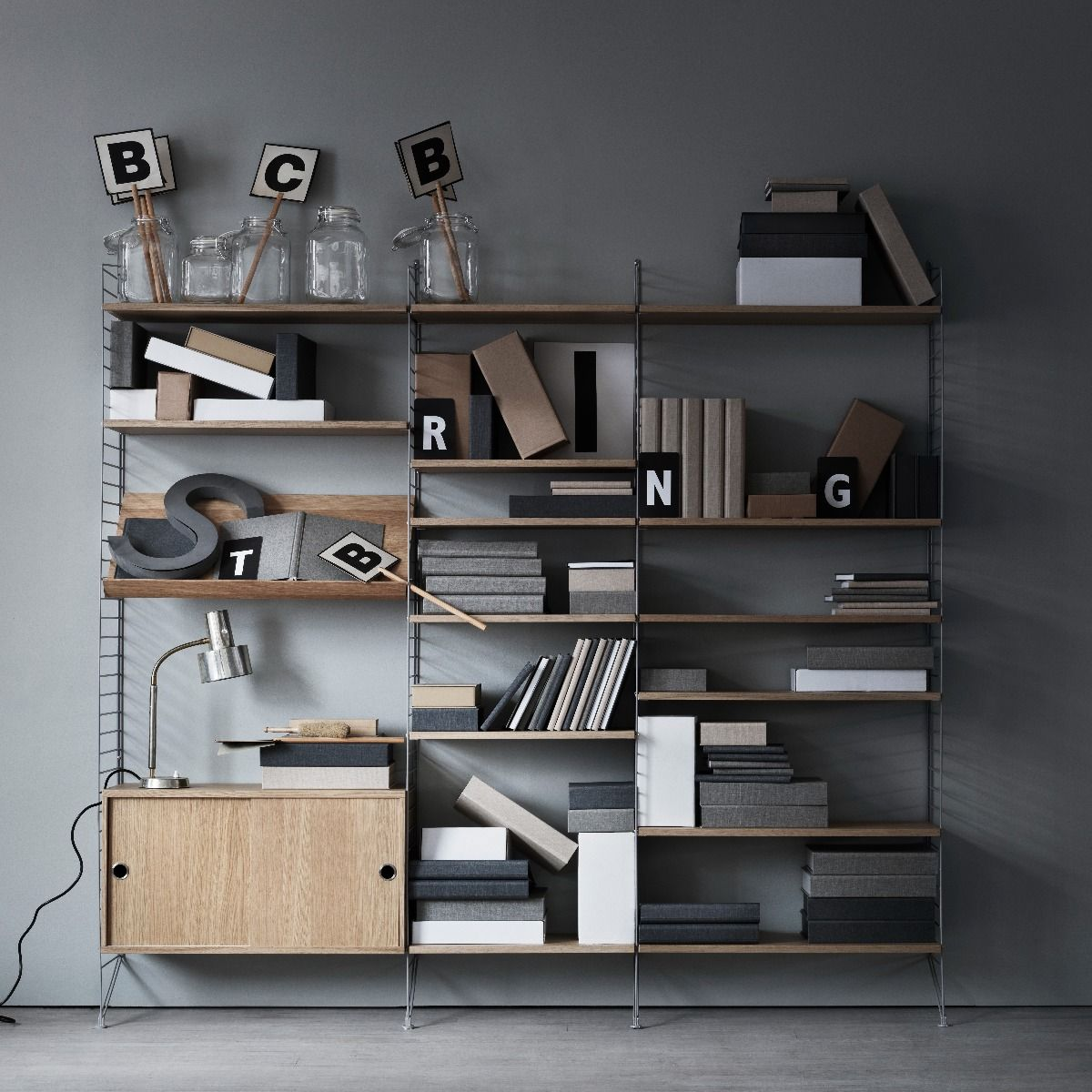 Oak and grey shelving system on a grey wall and boxes on the shelves