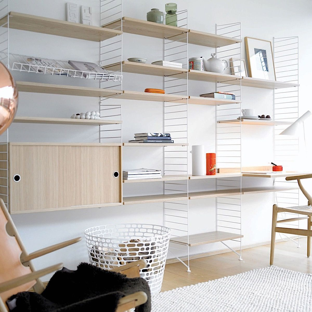 Oak and white String shelving system including wire magazine rack