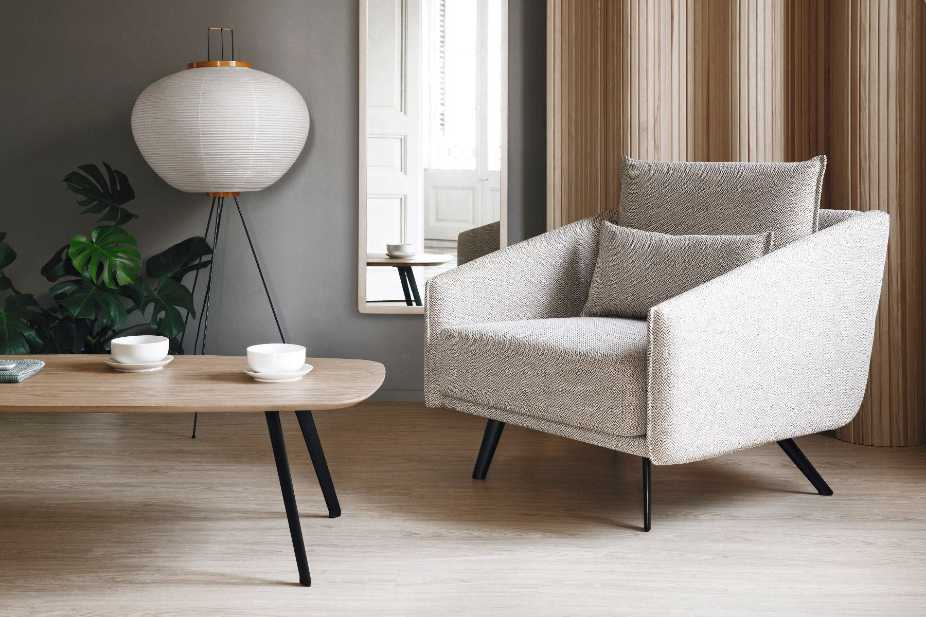 Stua Solapa coffee table oak with black legs  in front of a chair