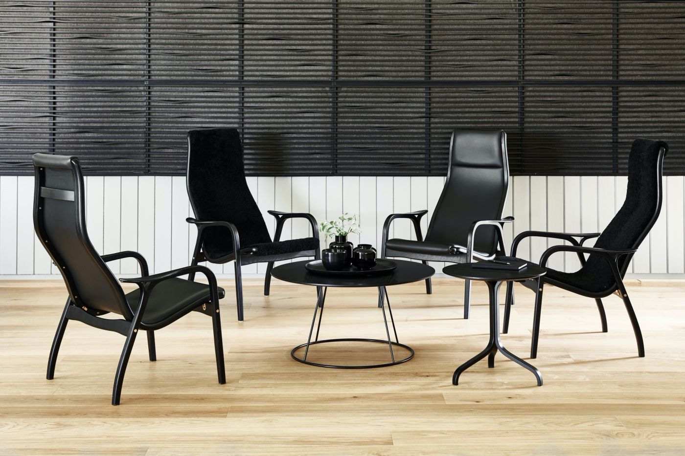 Four Swedese lamino chairs in black leather around a coffee table
