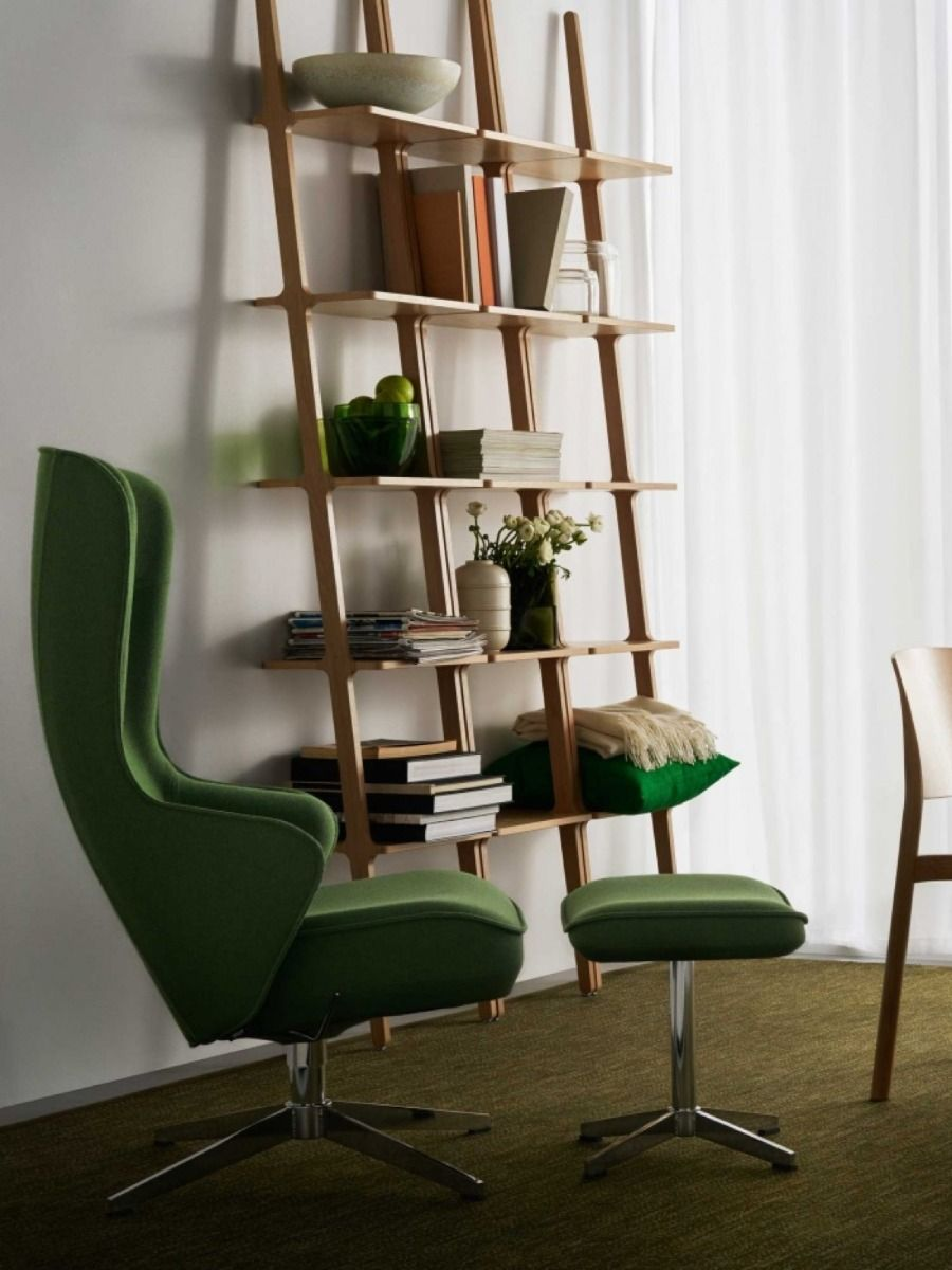 Three tall libri shelves in a room with a green chair