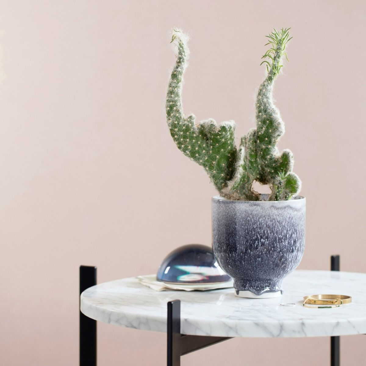 kahler grey unico flower pot with a cactus plant on a white marble table with a pink wall behind