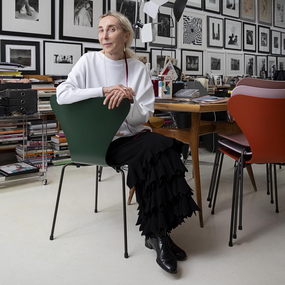 Carla Sozzani in her studio sitting on a fritz hansen series 7 chair